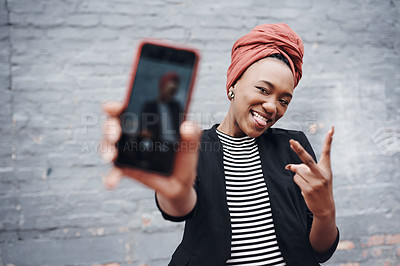 Buy stock photo Cropped portrait of an attractive young businesswoman taking selfies while gesturing the peace sign against a grey brick wall outside