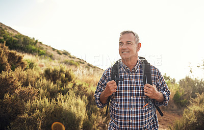Buy stock photo Shot of a mature man hiking through the mountains