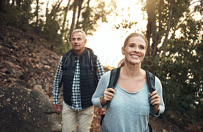 Buy stock photo Shot of a mature couple hiking through the mountains