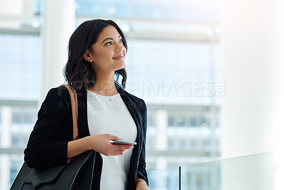 Buy stock photo Cropped shot of an attractive young businesswoman looking thoughtful while holding a smartphone in a modern office