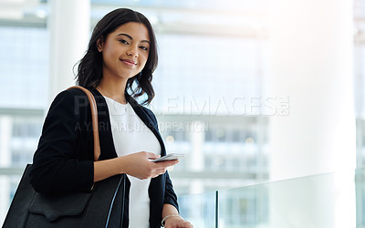 Buy stock photo Cropped portrait of an attractive young businesswoman holding a smartphone while standing in a modern office