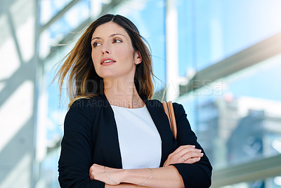 Buy stock photo Cropped shot of an attractive young businesswoman looking thoughtful while standing with her arms crossed in a modern office