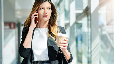 Buy stock photo Cropped shot of an attractive young businesswoman taking a a phonecall while walking through a modern office