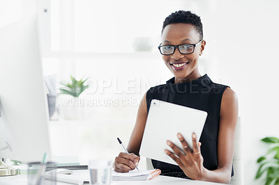 Buy stock photo Shot of a confident young businesswoman writing in a notebook and using a digital tablet in a modern office