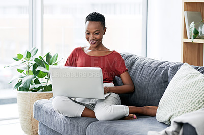 Buy stock photo Shot of a young woman relaxing on the sofa at home and using a laptop