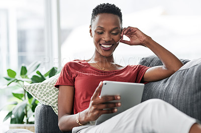 Buy stock photo Shot of a young woman relaxing on the sofa at home and using a digital tablet