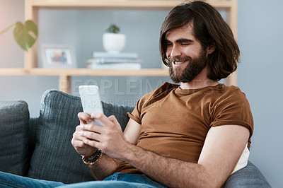 Buy stock photo Shot of a handsome young man using his cellphone while relaxing on a sofa in his living room
