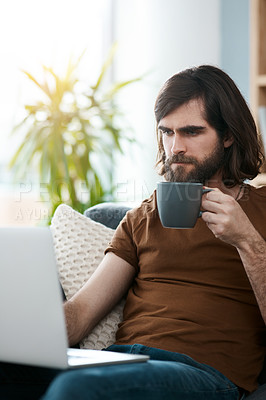 Buy stock photo Shot of a handsome young man relaxing the sofa in his living room