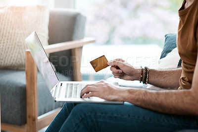 Buy stock photo Shot of an unrecognizable man holding a credit card and using his laptop while relaxing in his living room