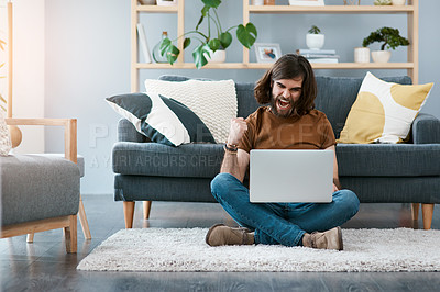 Buy stock photo Shot of a cheerful young man using his laptop while sitting on a carpet in his living room