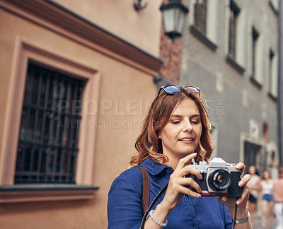 Buy stock photo Shot of a young woman taking pictures while exploring a foreign city