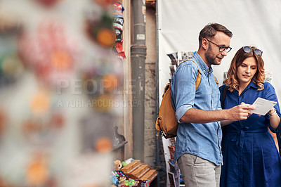 Buy stock photo Shot of a couple looking at post cards while in a foreign city