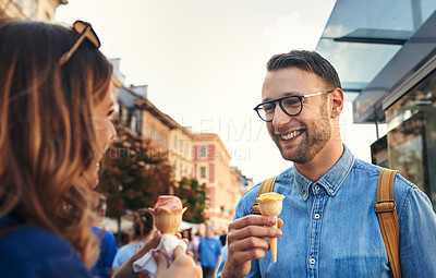Buy stock photo Shot of a couple having ice cream while out exploring a foreign city