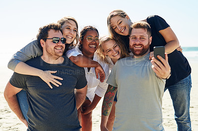 Buy stock photo Shot of a group of friends taking a selfie while spending time at the beach