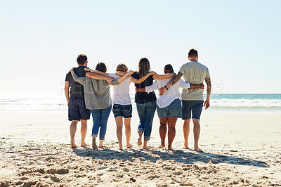 Buy stock photo Rearview shot of a group of friends standing together on the beach