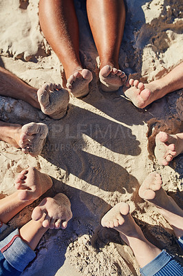 Buy stock photo Cropped shot of a group of unrecognizable people sitting barefoot on the beach