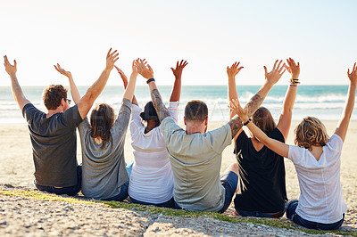 Buy stock photo Rearview shot of a group of friends sitting with their arms raised at the beach