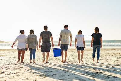 Buy stock photo Rearview shot of a group of friends spending the day at the beach