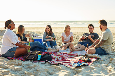 Buy stock photo Shot of friends enjoying drinks while spending the day at the beach
