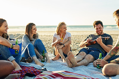 Buy stock photo Shot of a man playing an instrument while spending time with friends on the beach