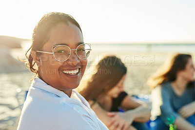 Buy stock photo Defocused shot of a young woman sitting on the beach with friends
