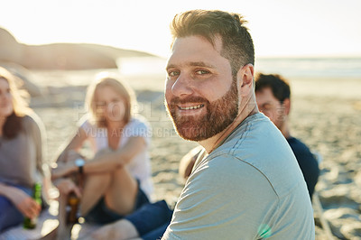 Buy stock photo Defocused shot of a man sitting on the beach with friends