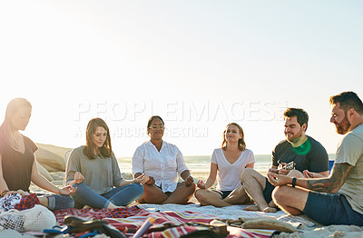 Buy stock photo Shot of a group of friends meditating while sitting together on the beach