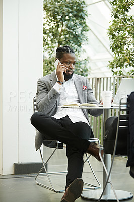 Buy stock photo Shot of a handsome young businessman taking a phone call while relaxing outdoors