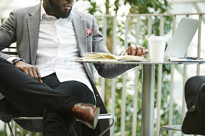 Buy stock photo Portrait of an unrecognizable business man doing some reading while relaxing outdoors