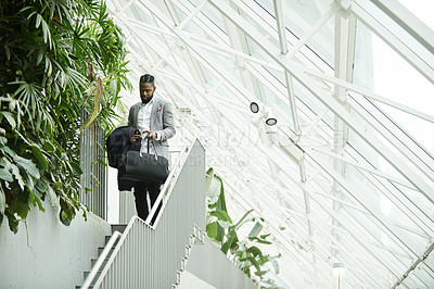 Buy stock photo Full length shot of a handsome young businessman heading down a flight of stairs
