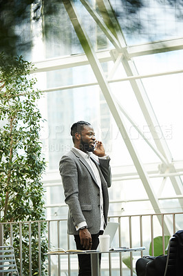 Buy stock photo Shot of a handsome young man taking a phone call while standing outdoors