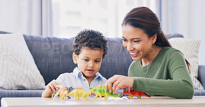 Buy stock photo Cropped shot of an attractive young woman and her son playing with his toy dinosaurs in their living room