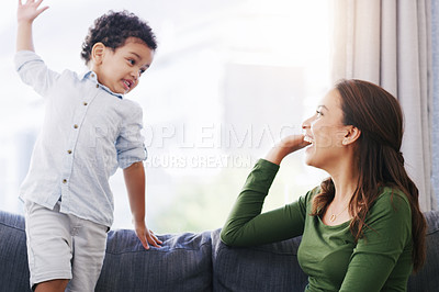Buy stock photo Cropped shot of an attractive young woman and her son high fiving in their living room