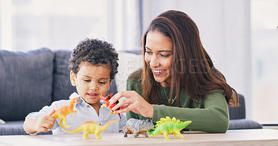 Buy stock photo Cropped shot of an attractive young woman and her son playing with his toy dinosaurs in the living room