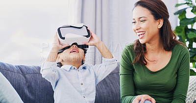 Buy stock photo Cropped shot of an adorable little boy playing with his virtual reality headset while his mother watches on