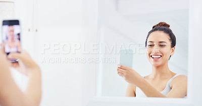 Buy stock photo Cropped shot of a young woman taking a selfie while standing in the bathroom