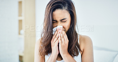 Buy stock photo Shot of a young woman blowing her nose with a tissue in her bedroom at home