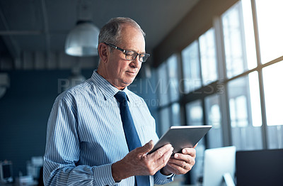 Buy stock photo Shot of a mature businessman using a digital tablet at the office