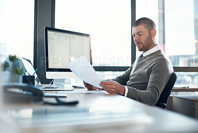 Buy stock photo Shot of a businessman working on paperwork at his desk