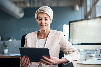 Buy stock photo Cropped shot of a mature businesswoman using a digital tablet at her desk