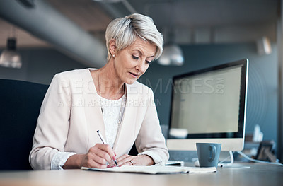 Buy stock photo Cropped shot of a mature businesswoman working on paperwork at her desk