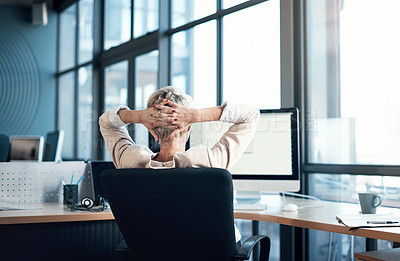 Buy stock photo Rearview shot of a businesswoman looking relaxed while sitting at her desk