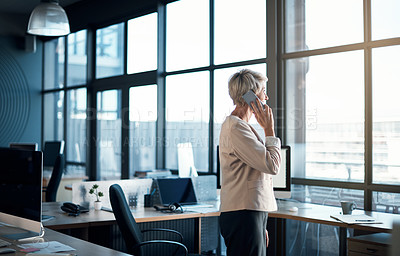 Buy stock photo Shot of a businesswoman talking on her cellphone in an office