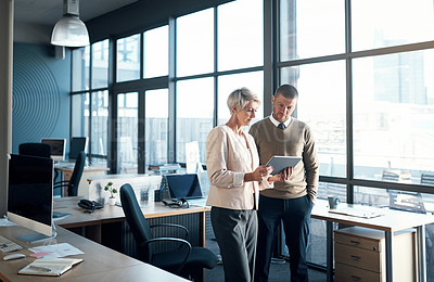 Buy stock photo Shot of two businesspeople discussing something on a digital tablet