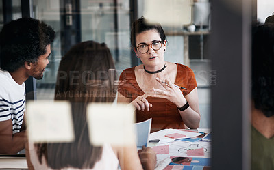 Buy stock photo Shot of a young designer having a meeting with her colleagues in an office