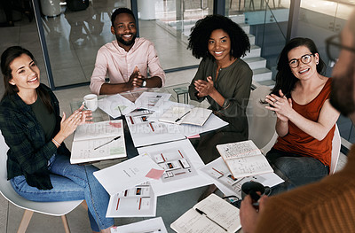 Buy stock photo Shot of a group of designers applauding during a meeting in an office