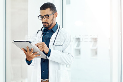 Buy stock photo Shot of a young doctor using a digital tablet in a modern hospital