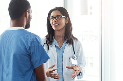 Buy stock photo Shot of two young doctors having a discussion in a modern hospital
