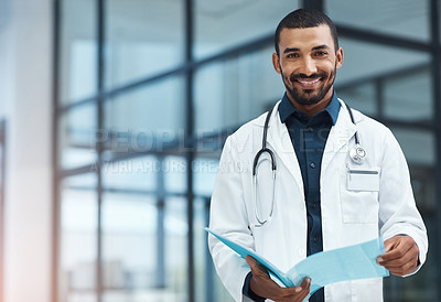 Buy stock photo Portrait of a young doctor going over the contents of a file in a modern hospital