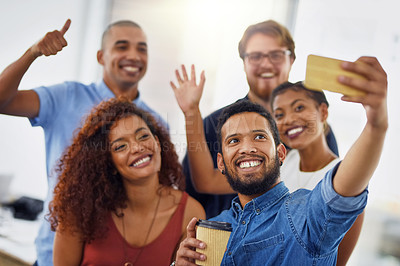 Buy stock photo Cropped shot of a group of cheerful young businesspeople taking a self portrait together inside of the office at work